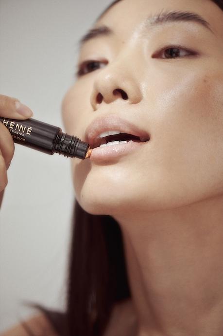 Asian woman applying Lip Serum to her lips.