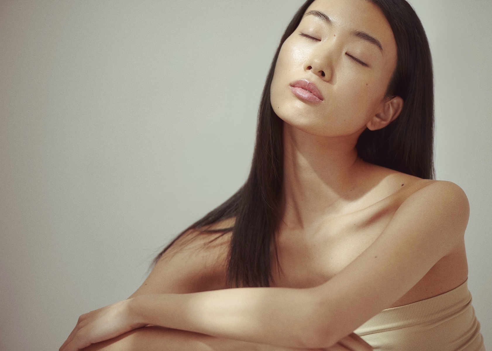 Asian woman relaxed with her eyes closed.