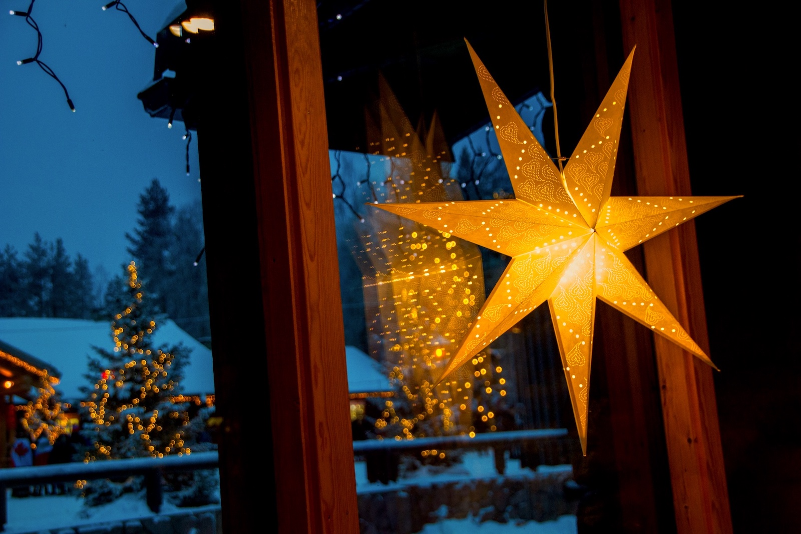 Christmas star hanging by window of a house in evening.