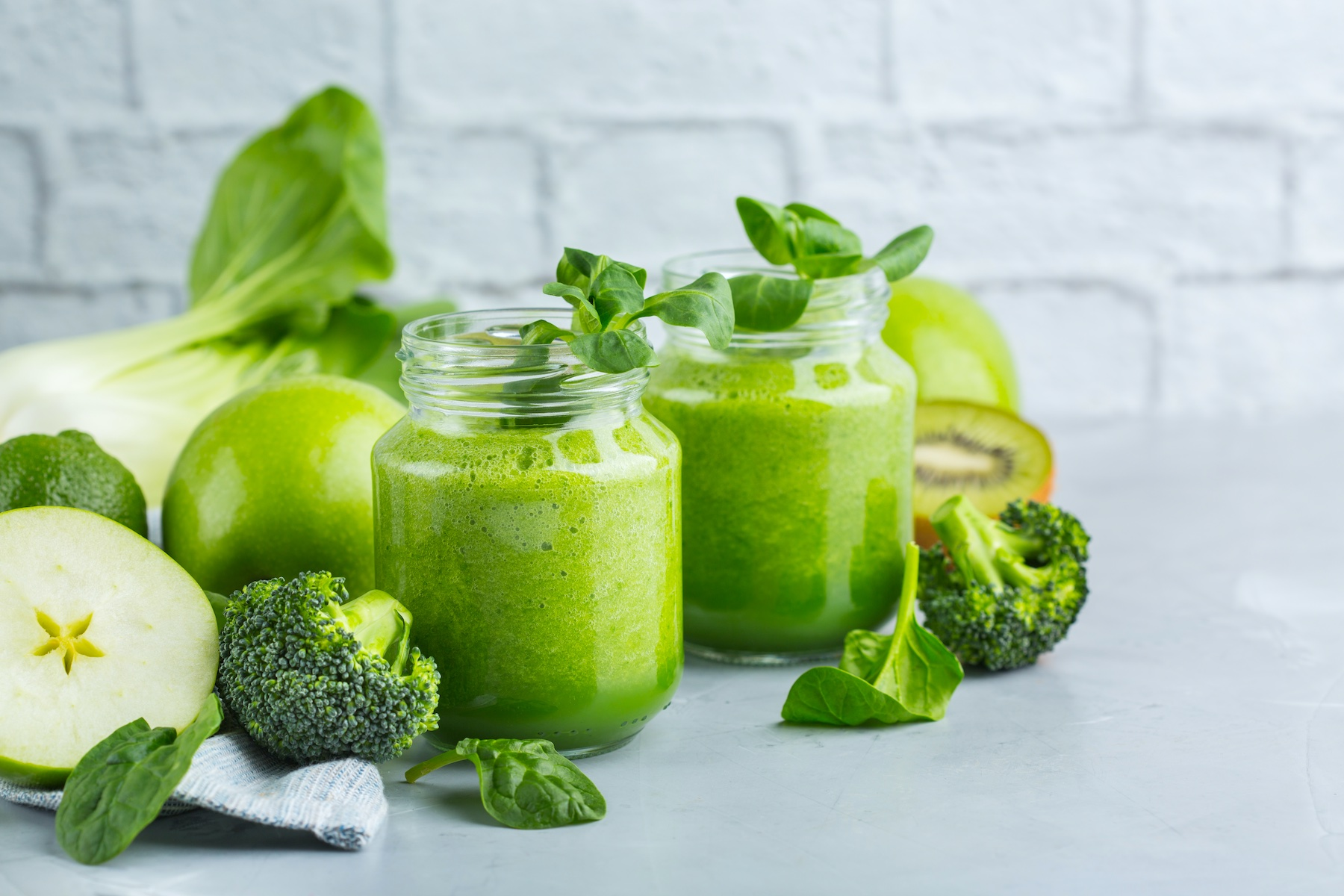 Two green juices in glass jars with green vegetables surrounding