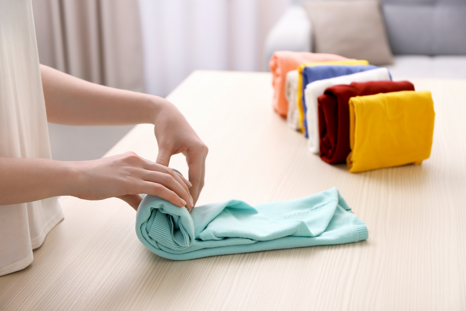 A woman's hands are folding clothes by rolling them