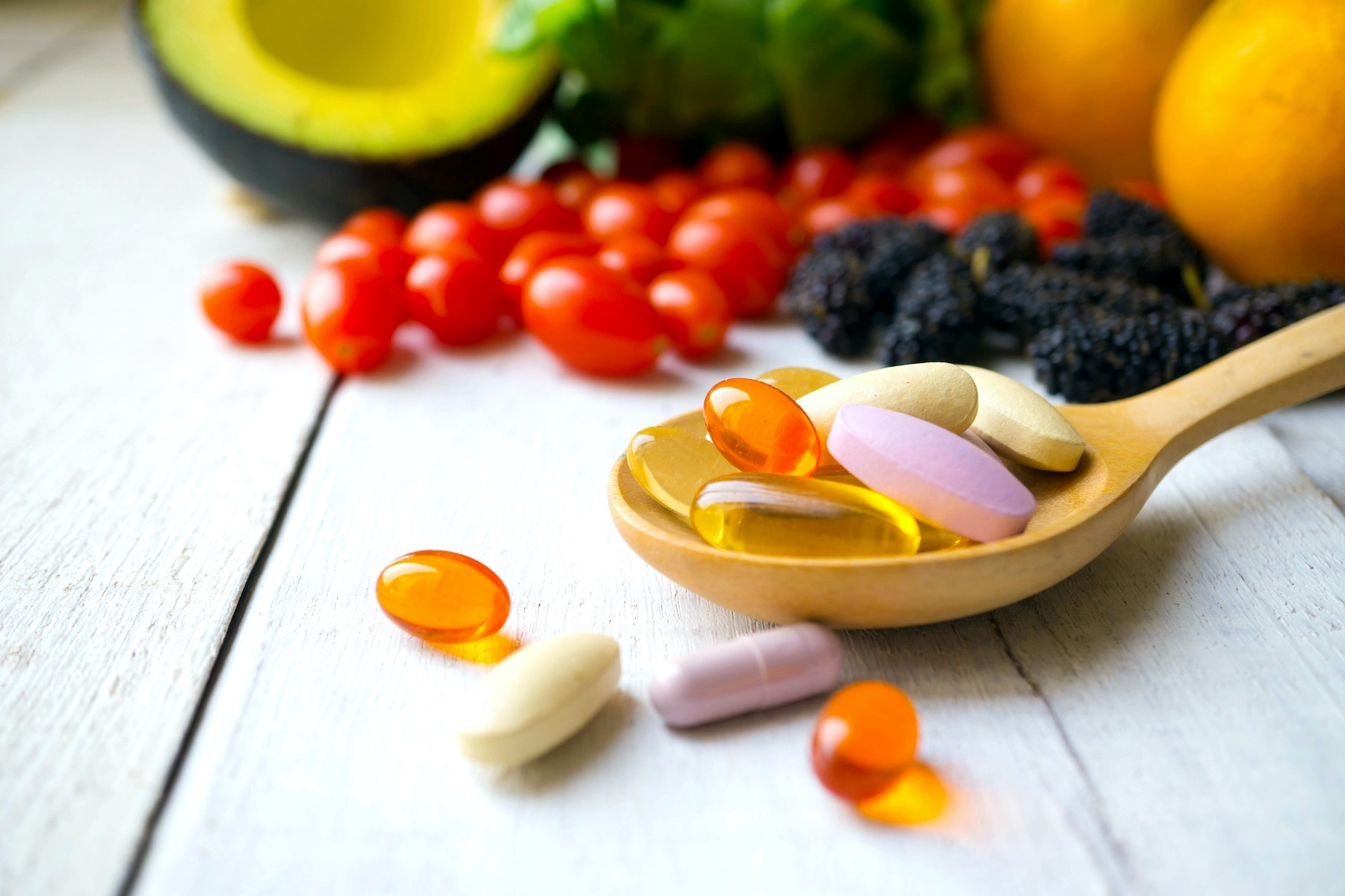Pills on a spoon with fresh produce in the background.