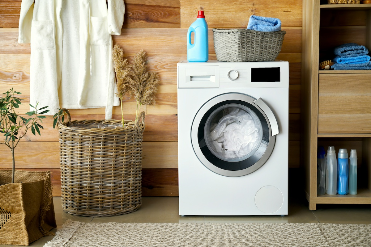 Washer with clothes inside with basket and laundry items