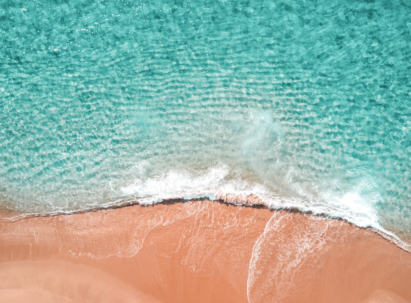 Aerial shot of ocean and sand