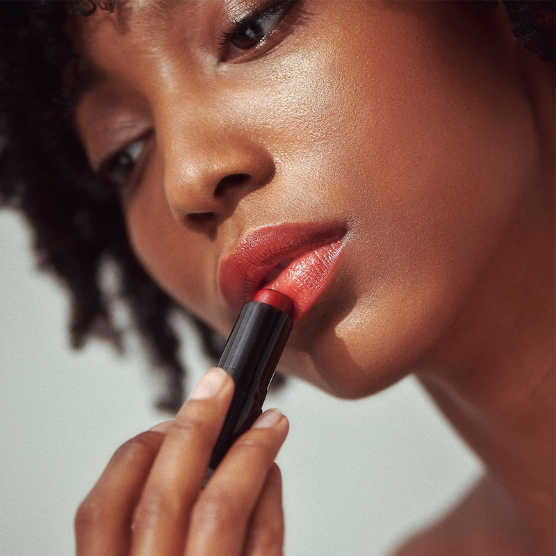 African American woman holding red lip tint
