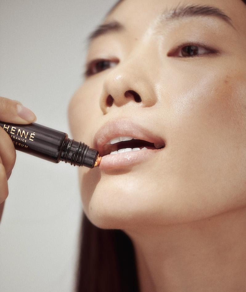 Asian woman applying Lip Serum
