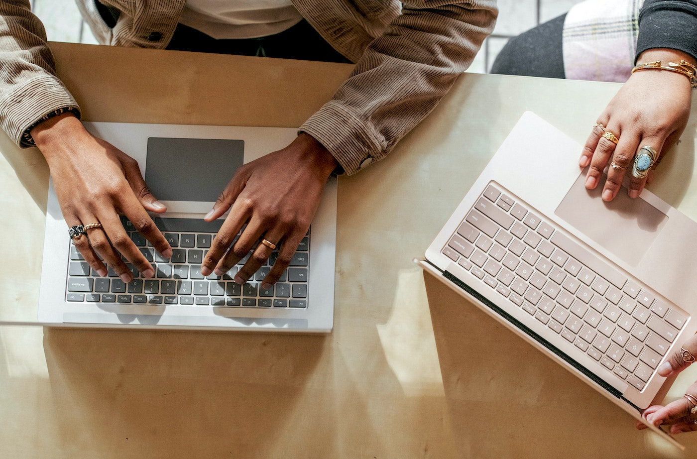 Two people's hands with laptops
