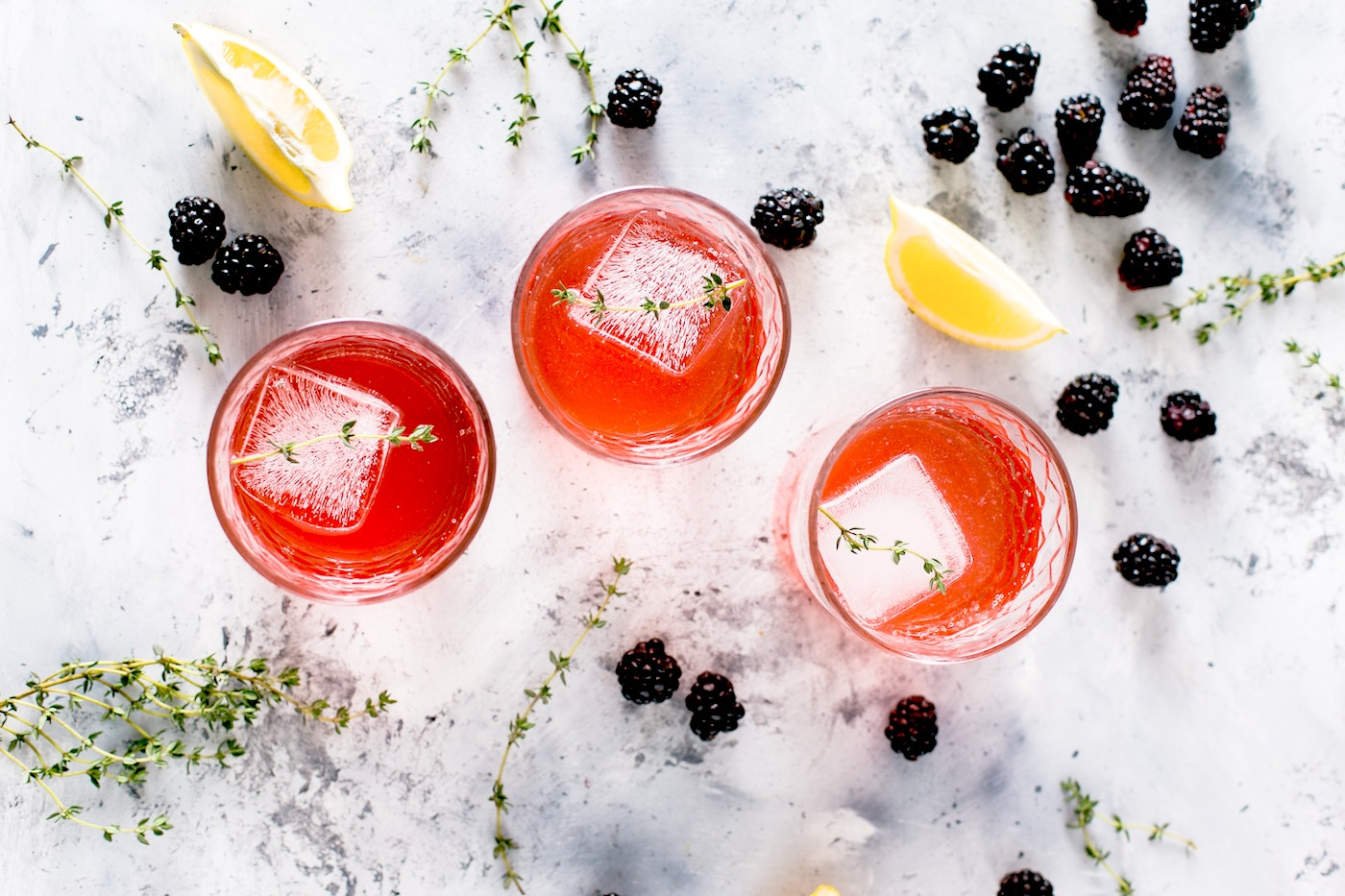 Red cocktails with blackberries around them
