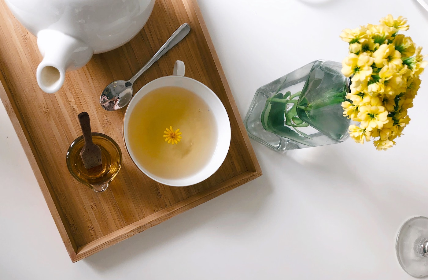 Tea on brown tray with yellow flowers