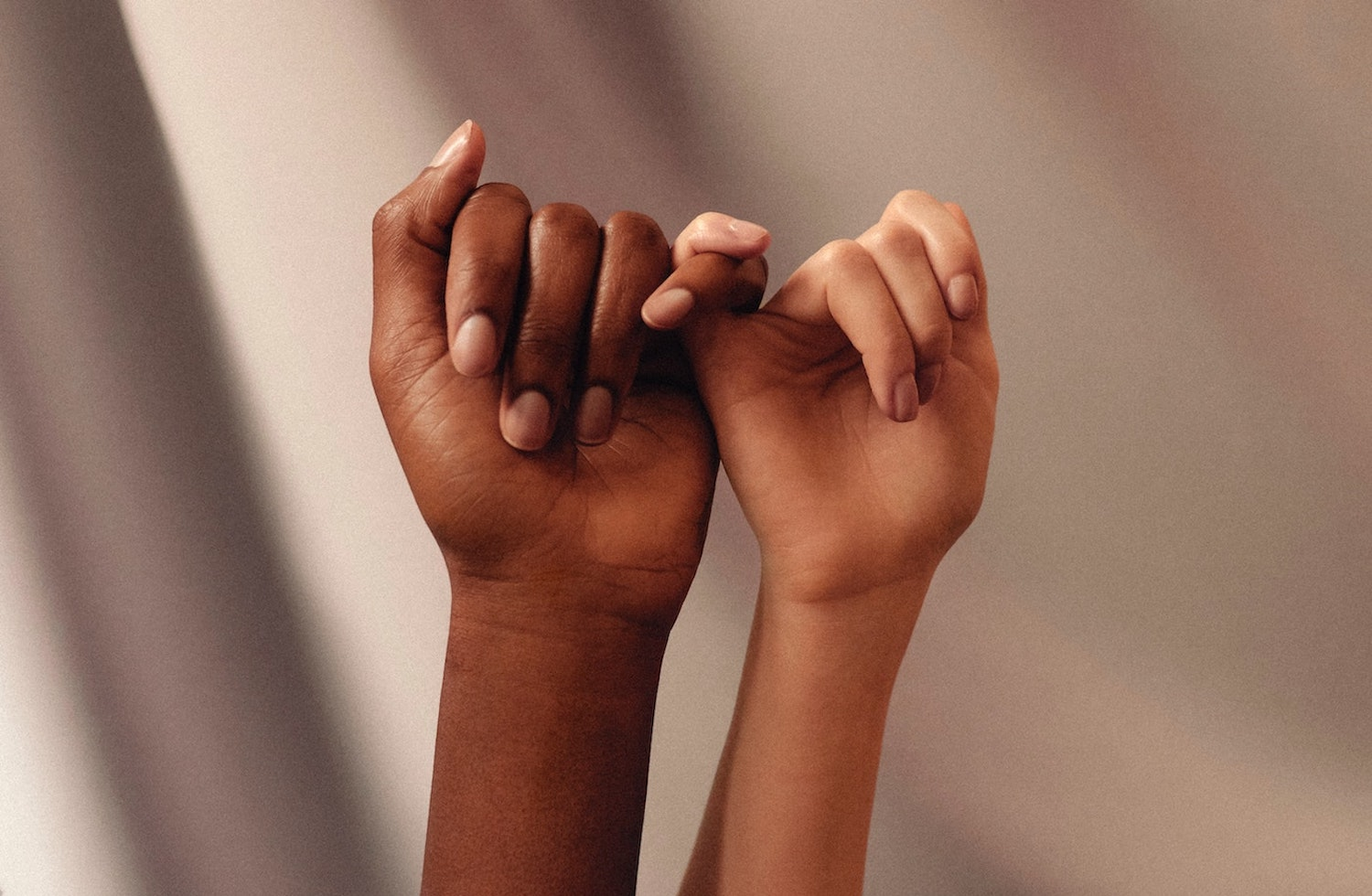 Two hands with interlocking pinky fingers