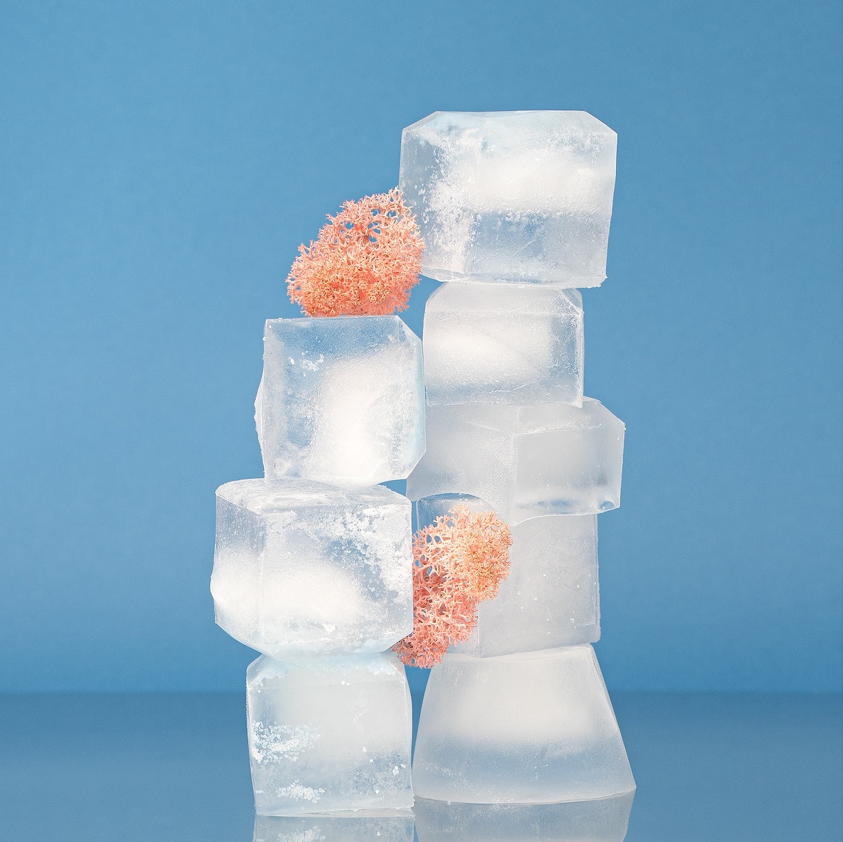 Ice cubes stacked on blue background